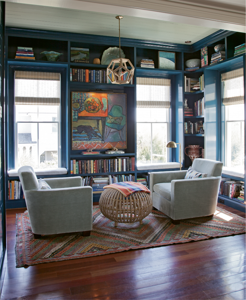 "Reading Rainbow - For this small library, Cortney Bishop designed floor-to-ceiling shelves and built-in window seats and had them painted a shade of blue that matches the deep waters of the sea. Now filled with the homeowners' books, family photos, artwork, and other keepsakes, it has become one of the couple's favorite spaces.  Location: Sullivan's Island, (owned by Lynne and  Steve Hamontree) Issue: September 2014, ""Carolina by Way of California""  Photographer: Julia Lynn"