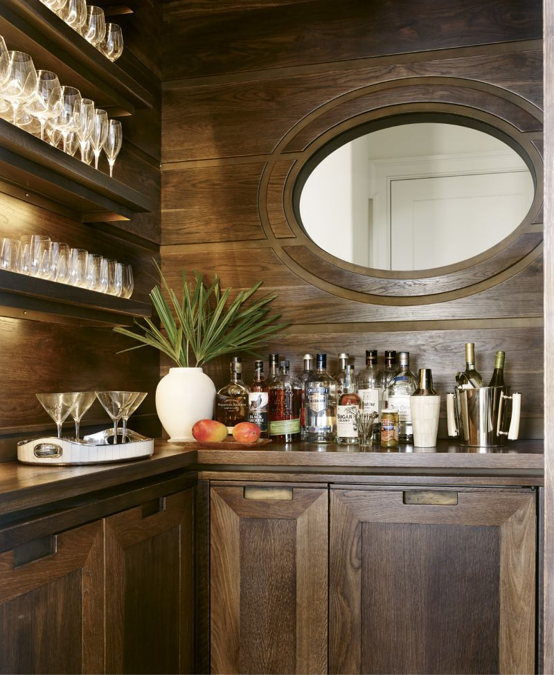 Custom cypress cabinetry by local firm ECR Joinery and an oval-shaped interior window distinguish the bar, which separates the kitchen and living room.