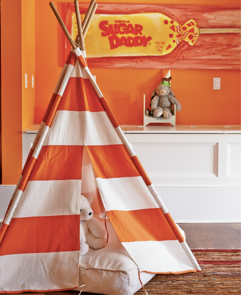 "Orange Crush - A new stairwell allowed a young family easy access to this attic space. Vibrant orange paint, built-in toy storage, and a striped teepee made it a spunky playroom.  Location: South of Broad (Villa Margherita, circa 1895,  owned by Mary and Stephen Hammond)  Issue: September 2015, ""Viva La Villa""  Photographer: Brie Williams"