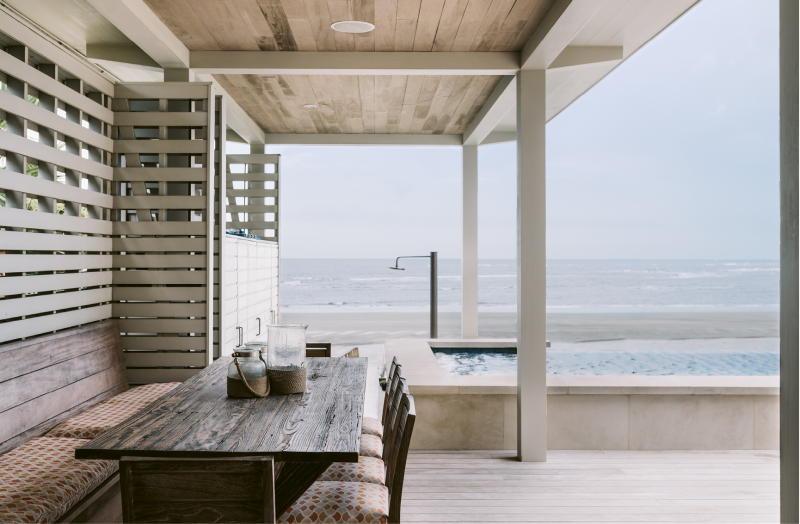 "Elevated Entertaining - Dufford Young Architects nested an elevated deck of garapa and a zero-edge pool into the house, creating the family's entertaining headquarters. A slatted wall offers privacy while allowing breezes to flow through the dining area with a large reclaimed wood table crafted by Landrum Tables.  Location: Isle of Palms  (owned by Suzanne Fine and Christian Salomone) Issue: September 2016, ""Laid-back Luxe""  Photographer: Katie Charlotte"