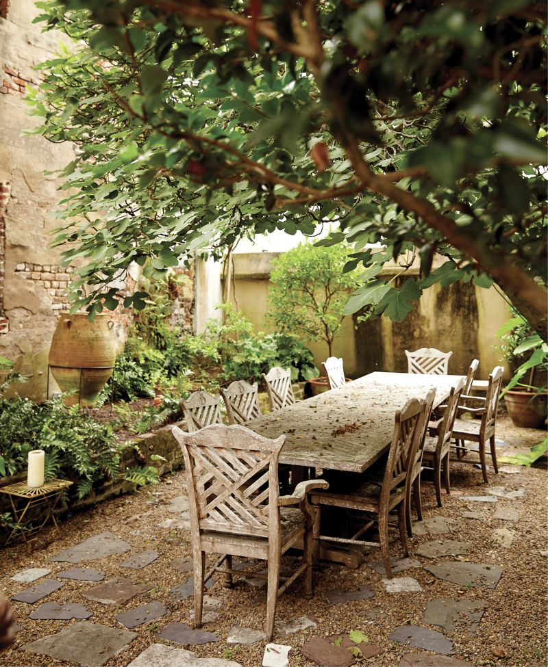 """Garden Party - Tucked behind the patinaed stucco and brick of a Rainbow Row town house, this courtyard is a lovely alfresco dining room featuring potted citrus trees, such as lemon and tangerine.  Location: Rainbow Row (circa-1785 Georgian row house, then owned by Suzanne and Peter Pollak)  Issue: February 2017,  """"Mix Master""""  Photographer: Leigh Webber"""