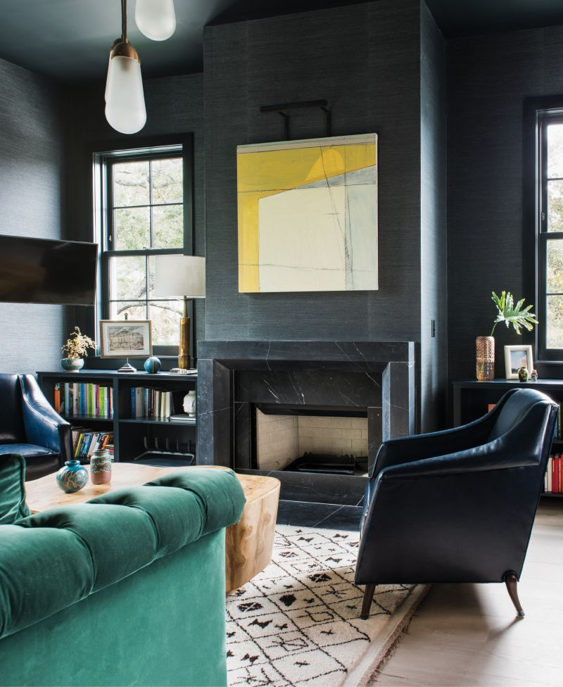 "Amp Up the Ambiance - The rich hues and textures in this High Battery library beckon for hours of rest, reading, and relaxation. For this cozy-meetsmasculine space, interior designer Cortney Bishop covered the walls in Phillip Jeffries's ""Manila Hemp"" paper in ""charcoal"" and had the Hickory Chair sofa upholstered in an emerald-green velvet by Ralph Lauren. Over the fireplace, an abstract work by Frank P. Phillips adds a sunny pop of color.  Location: Downtown, South  of Broad, owned by Molly and  Ted Fienning  Issue: March 2018, ""High Style on the Battery""  Photographer: Katie Charlotte"