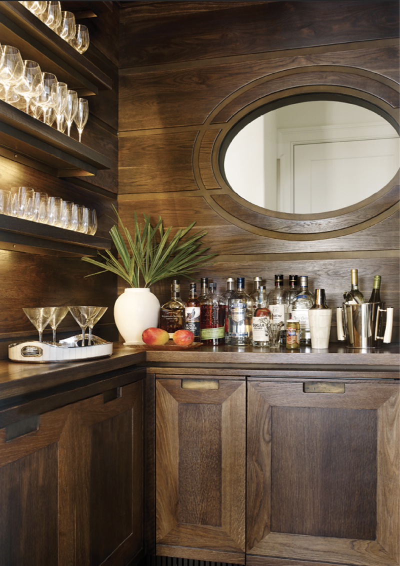 """Handsome Hideaway - Custom cypress cabinetry by local firm ECR Joinery and an oval-shaped interior window distinguish this bar, which separates the kitchen and living room.  Location: Kiawah Island, (owned by Leah and Gee Aldridge) Issue: July 2018, """"Style & Substance""""  Photographer: Emily Jenkins Followill"""