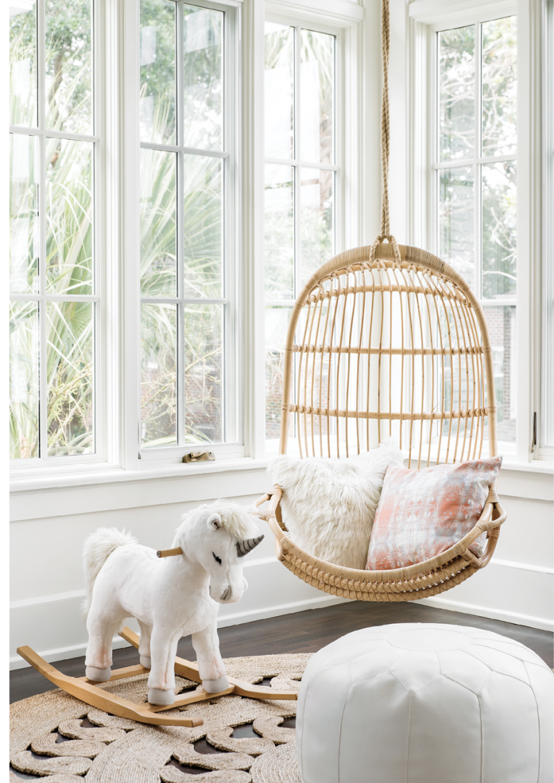 "Hang Time - Kid-friendly furniture, like the Serena & Lily hanging chair and white leather pouf, make this a primo seat in a light-filled playroom.  Location: South of Broad (owned by Allison and Parker Green)  Issue: March 2019, ""What's Old Is New Again""  Photographer: Katie Charlotte"