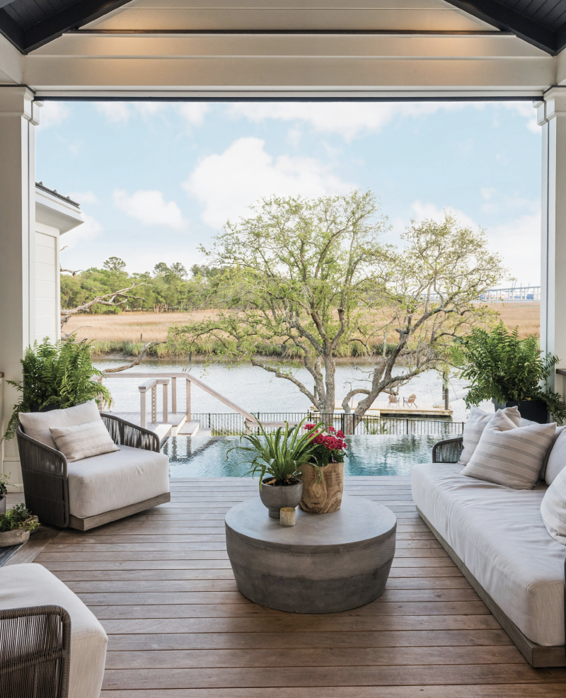 """Weather the Elements - Outdoor-friendly furnishings and materials—performance fabric on the teak lounge chairs and sofa and planks of hardy, rot-resistant garapa—make this covered space overlooking Ralston Creek a sleek yet comfy respite most of the year.  Location: Daniel Island Issue: July 2019, """"High Style Haven""""  Photographer: Marni Rothschild Durlach"""