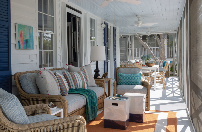 """In the Zone - With its views of the Atlantic, this screened space is the most popular spot in the house. Dividing this long porch into two areas—living room in the foreground and dining for 10 in the distance—increases its usefulness and allows many people to enjoy it at once. Furnishings include classic rattan seating from Lane Venture with pillows from Candelabra, and a dining table with handmade rattan chairs from Sika Design USA that will patina to a light gray finish.  Location: Sullivan's Island  Issue: August 2019,  """"Beachy Keen""""  Photographer: Julia Lynn"""