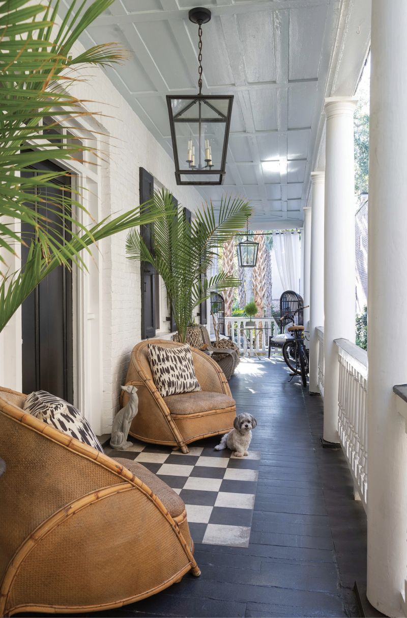 """Old School Meets New - While the piazza floor of this circa-1840 Greek Revival single house is painted in traditional """"Charleston green"""" and its ceiling the customary pale blue, the circa-1930s rattan chairs and bold patterned pillows hint at the blend of modern and vintage styles within.  Location: Ansonborough (owned by Betsy and Bruce Finley)  Issue: February 2020, """"A Twist on Tradition""""  Photographer: Julia Lynn"""