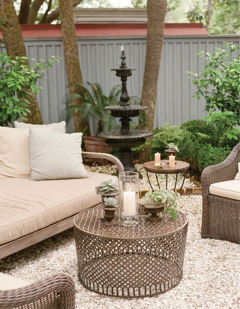 To turn a garden alcove into an inviting cocktail nook, Lynn arranged outdoor furniture and added candles and potted plants to enhance an oyster tabby patio.