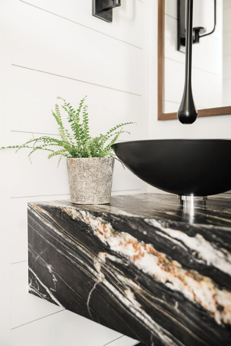 A black Alape basin and ceiling-hung faucet in the powder room