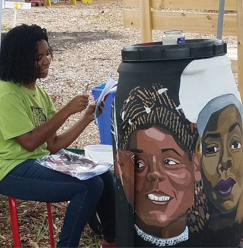 Anik Hall refreshes the painting on a compost tumbler.