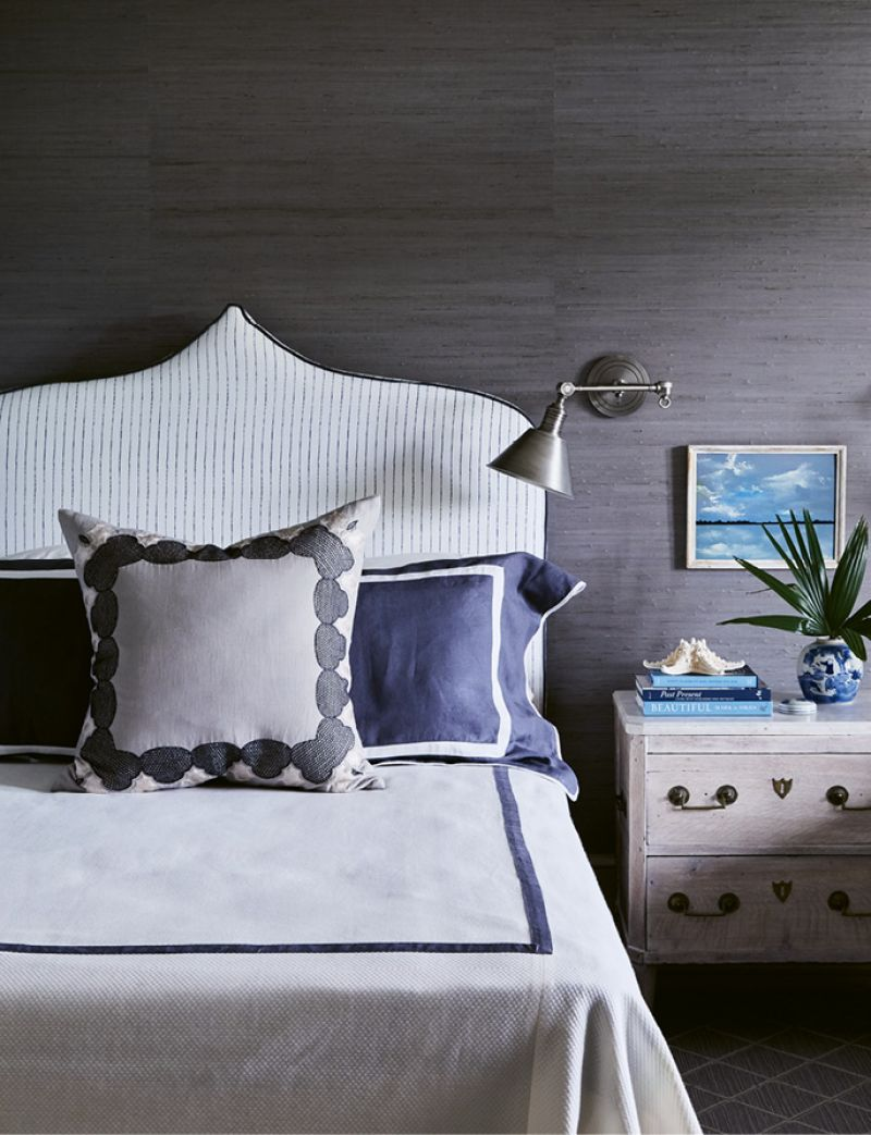 The guest bedroom's steely grey-blue grasscloth-covered walls allude to the creek at night. A headboard covered in a Christopher Farr indigo-striped linen, duvet by Leontine Linens, and 19th-century nightstand from Parc Monceau Antiques in Atlanta complete the space.