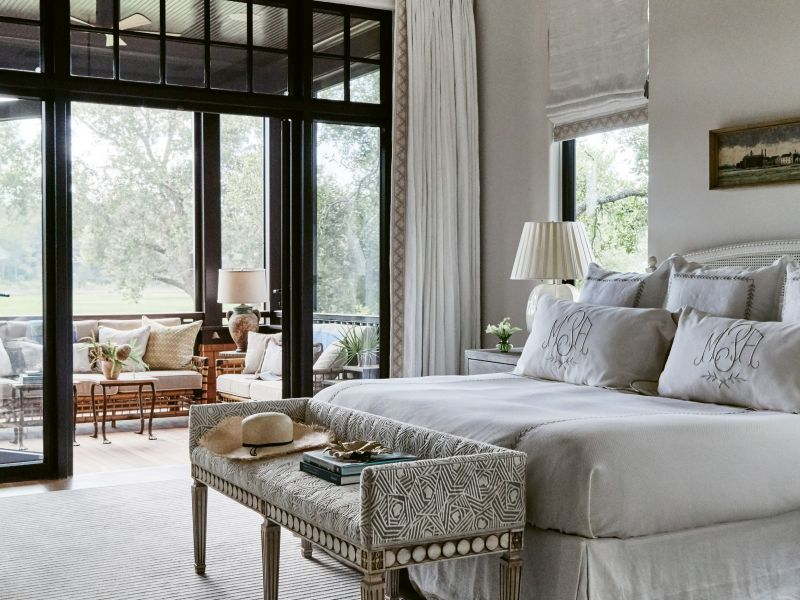"SERENE SCENE: The master suite is a haven of serenity—from the freestanding soaking tub with views of the trees to a quaint and comfortable screened porch, perfect for lounging with coffee. Custom pillows brighten the space, including two wrapped in a brightly colored Clarence House fabric and lumbar varieties in Lucas's own line, House of Harris. Vintage-inspired pieces, such as the Henredon ""Arianna"" bench in Mokum fabric, create a feeling of timelessness"