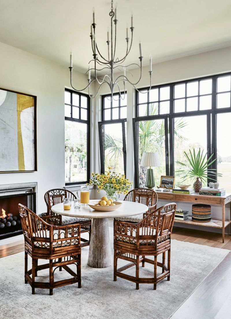 NATURALLY ELEGANT: Henselstone three-tilt transom windows from Germany give definition to the airy breakfast room, which is outfitted with organic furnishings, including a travertine pedestal table from a Palm Beach antiques shop and vintage Brighton rattan armchairs.