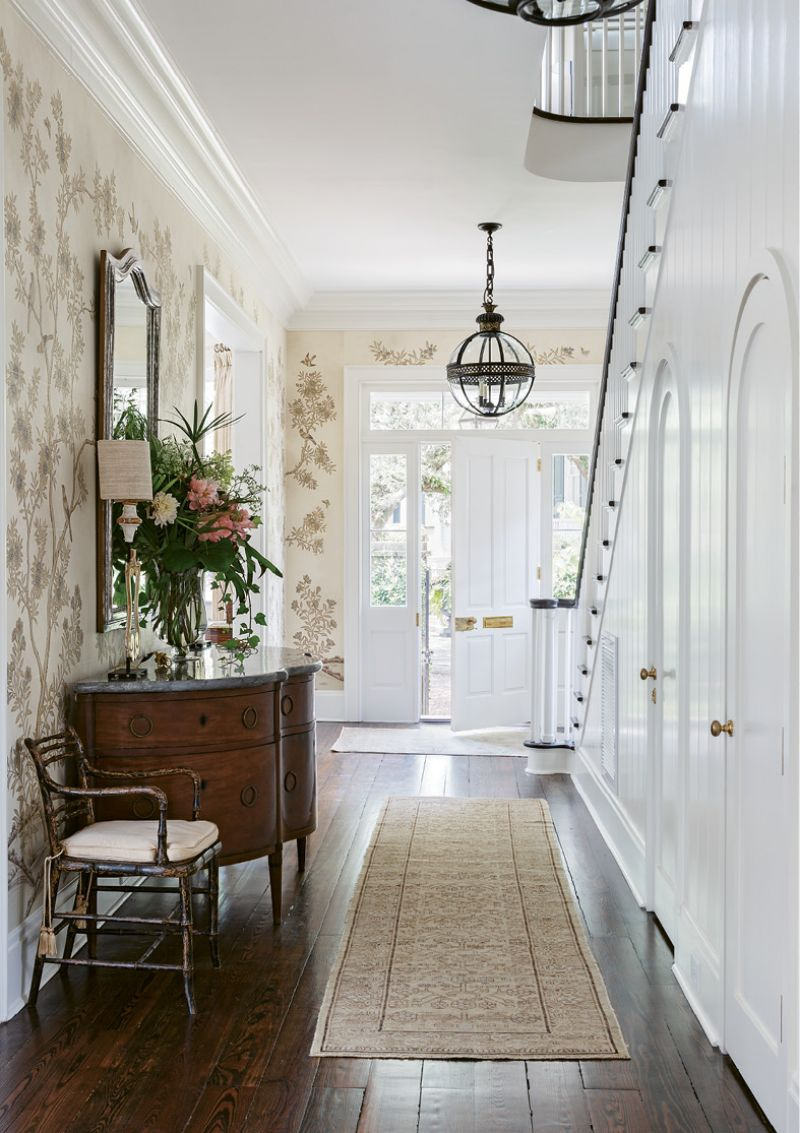 """HAUTE ARRIVAL: The entrance hall adds a dash of drama courtesy of exquisite Gracie """"Parchment Vista"""" wallpaper. Shades of cream together with gilt and silver produce a mesmerizing effect, complemented by the curves and scale of a circa-1850 stone-topped Italian buffet from Foxglove Antiques. Two English Regency armchairs from Charleston's Golden & Associates Antiques round out an eclectic mix of European pieces."""