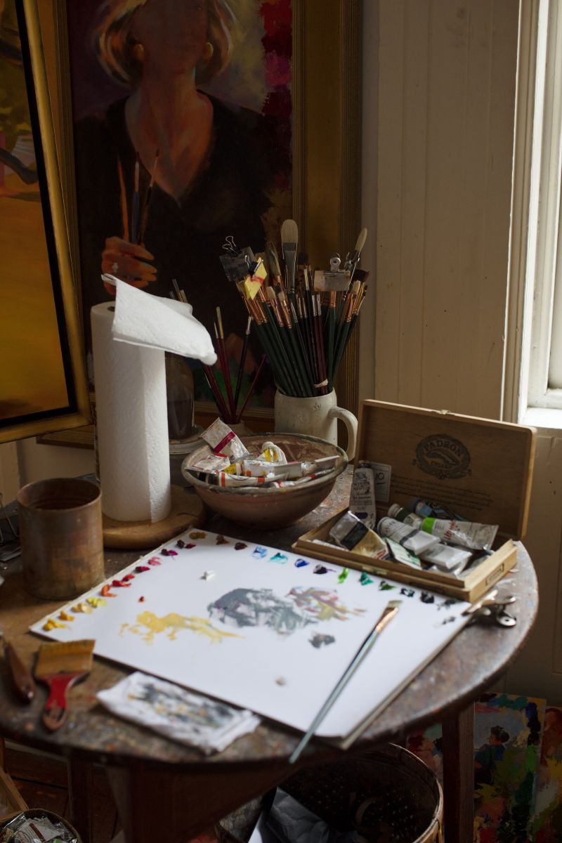 A ceramic mug filled with brushes and tubes of oil paint rest on a cricket table, layered in a paint-flecked patina after decades of use.
