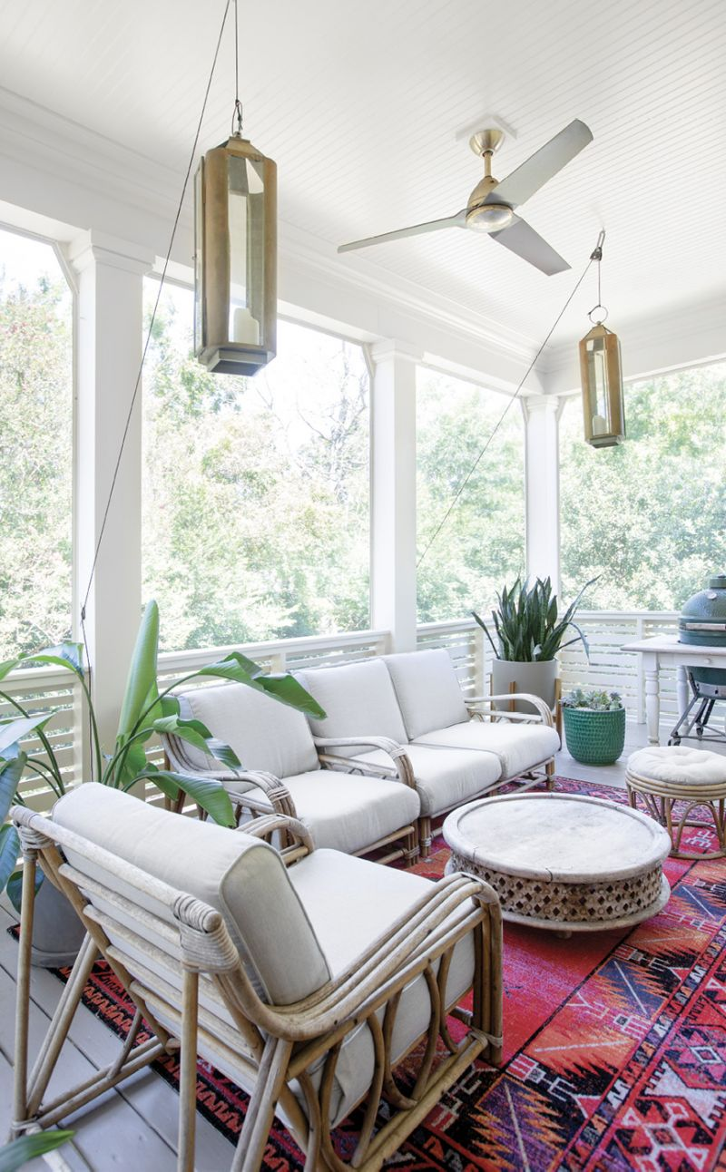 Chill & Grill: Newly screened-in, the back porch off the main living area offers more space for cooking and entertaining. Erin had the vintage rattan seating recovered by Aiden Fabrics, and Spence created a pulley system for the lanterns.