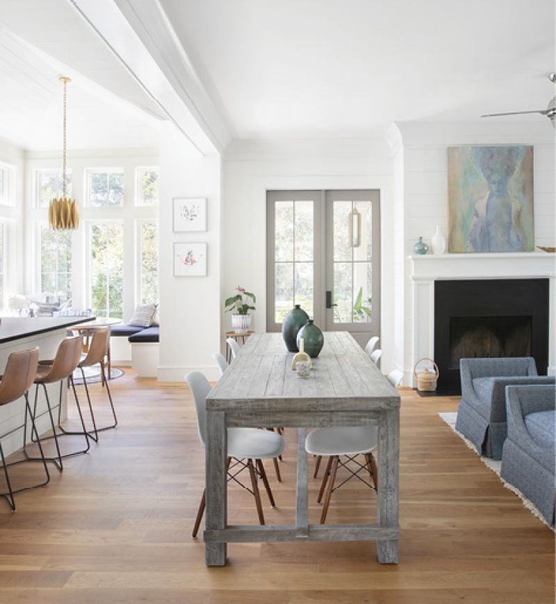 """Sit A Spell: In a home designed for entertaining, seating is a main priority. """"Slope"""" leather counter stools from West Elm line the island, while a bevy of mod molded-plastic chairs surround the rustic trestle table from Celadon. The central spot is in use most days, whether it's dinner for two or game night with friends"""