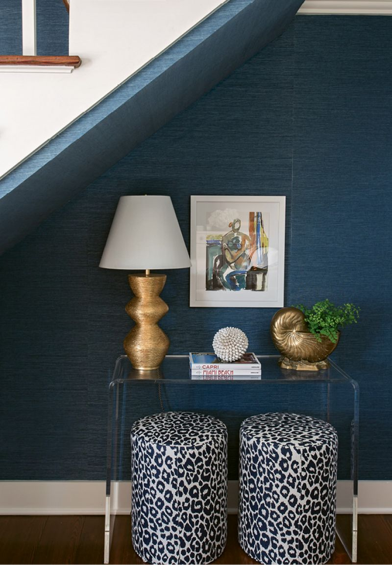 Similarly, a Lucite console disappears into a small nook under the stairs, allowing cherished pieces, such as the Anne Darby Parker painting, to shine.