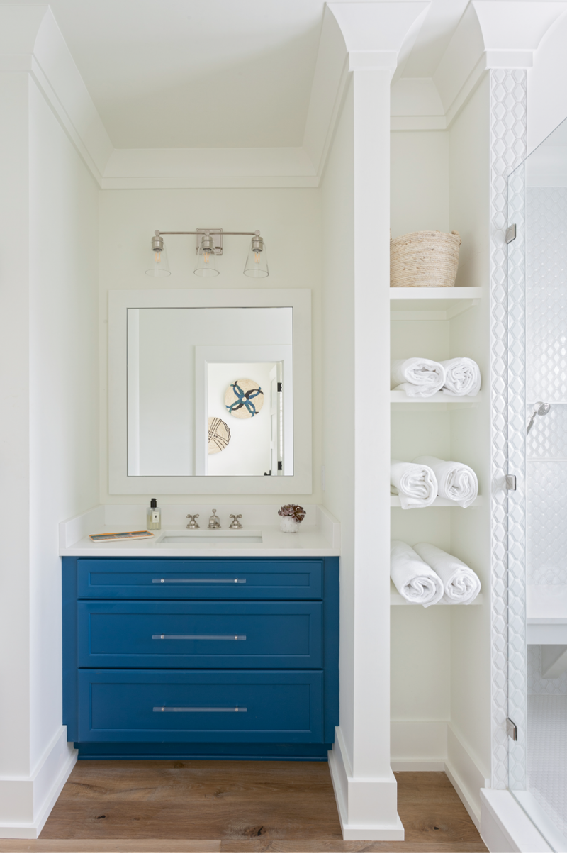 "A Pop of Color: The daughters share this remodeled bathroom, which was redesigned to afford a much larger shower space, complete with a bench and finished in subway tile from Melcer Tile. Custom cabinetry from Spartina Cabinets is offset by the Benjamin Moore ""Simply White"" wall color and illuminated by a vanity light in polished nickel from Carolina Lanterns."