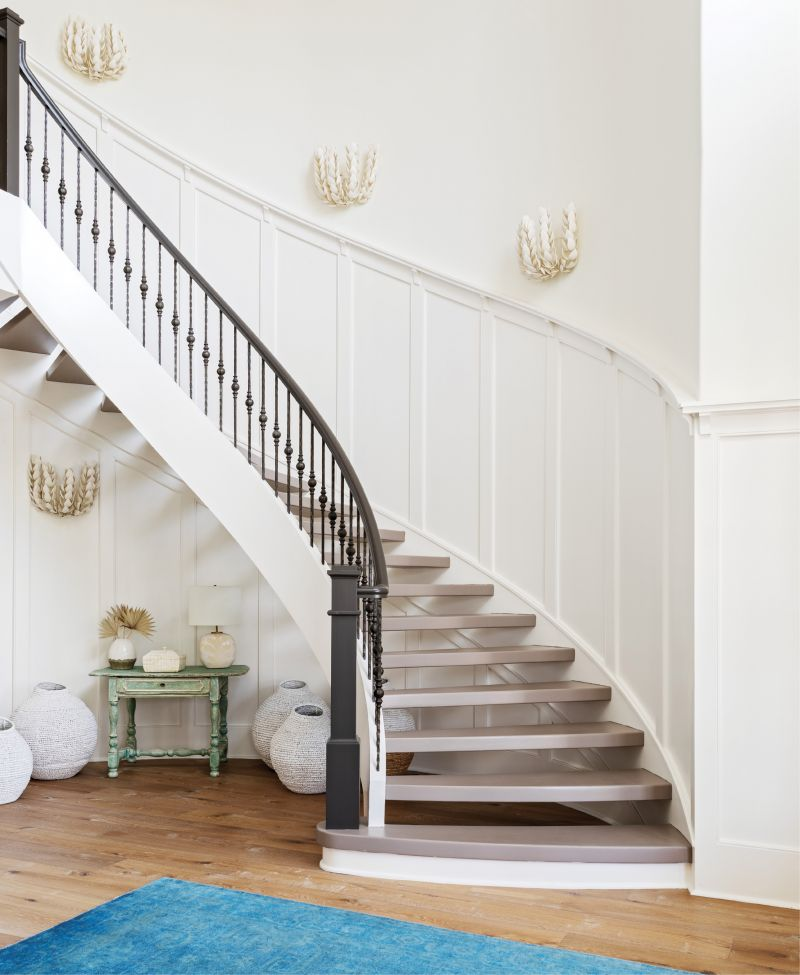 """WELCOME IN: """"It was a beautiful canvas to work with,"""" says interior designer Allison Elebash of the Leonard home, adding that its bones—including the foyer's custom millwork and sweeping floating staircase—needed only cosmetic updates. She painted stair treads Farrow & Ball's """"Charleston Charm"""" and installed white oak floors throughout the house to hide sand and fur. An azure rug from Antiques of South Windermere, seafoam-painted table from Acquisitions Interiors, woven jugs from GDC Home, and Palecek """"Coco Magnolia"""" sconces (fashioned from hand-cut coconut shells) ground the space in its coastal locale."""