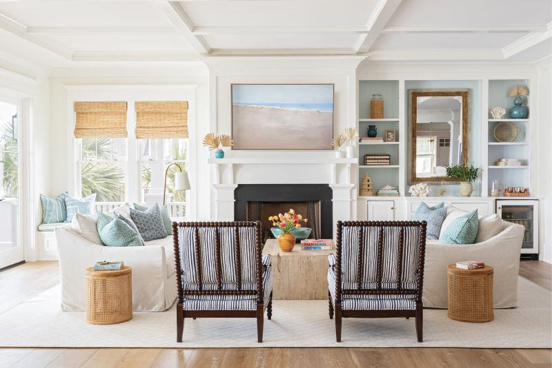 """OCEANSIDE OASIS: In the heart of the home, natural elements—like a wooden coffee table from Celadon, cane end tables from GDC Home, and a wool rug—mix with performance fabric-outfitted furnishings for an unfussy, beach-friendly vibe. A beach scene by Shannon Wood, pillows from Celadon, and the wet bar's back wall—painted Benjamin Moore's """"Ocean Air""""—underscore the sea-inspired palette."""