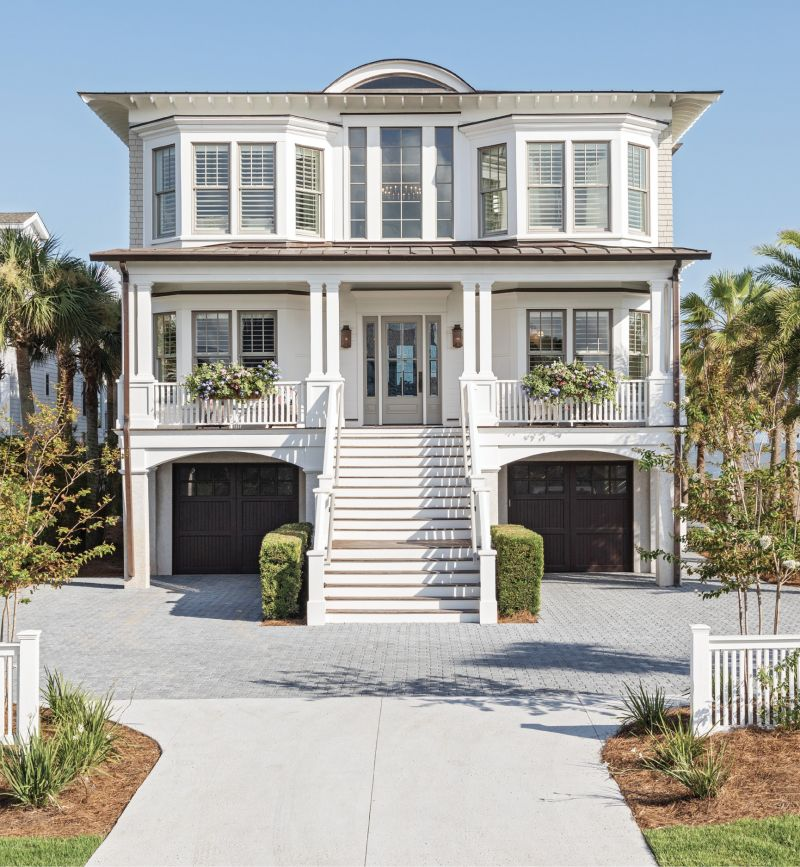RIGHT AT HOME: Last summer, San Diego residents Tom and Amy Leonard—along with their three sons, as well as wheaten terriers Charlie and Oliver—made this oceanfront Isle of Palms house their second home. Fresh exterior paint and a total overhaul of the yard and hardscape perked up the property's curb appeal. Relocating the driveway gave the home symmetry, while adding a pair of window boxes and painting the porch ceiling a pale blue upped its Lowcountry charm.