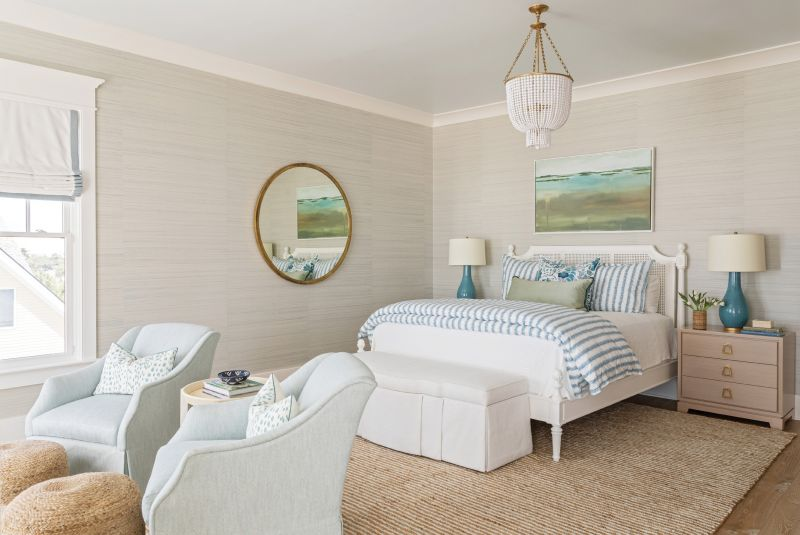 TOTALLY ZEN: Upholstered furnishings, grasscloth wallpaper, and a beachy palette make the primary bedroom a serene retreat. French doors lead out to a pergola-shaded private deck overlooking the ocean.