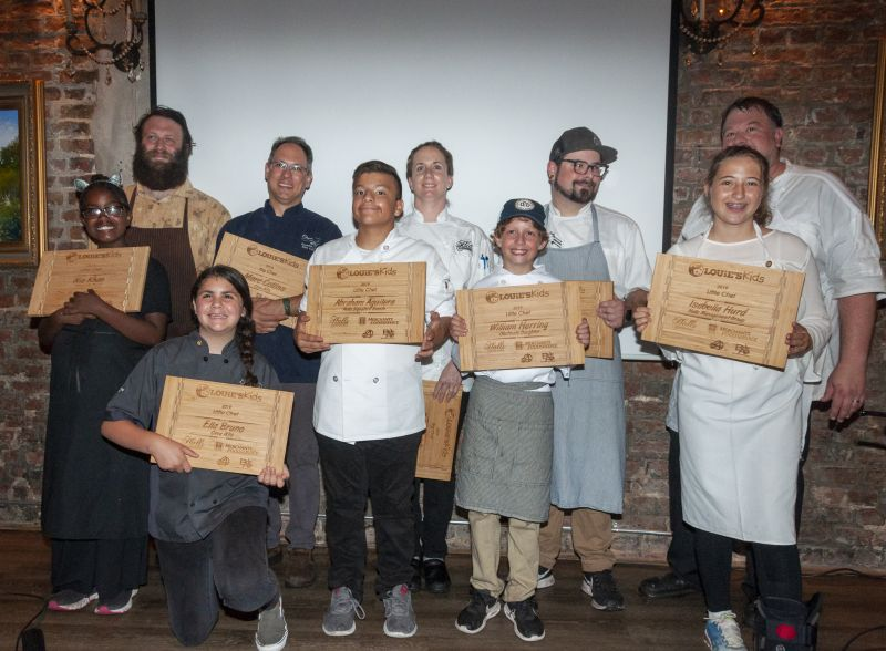 Bob Cook, Marc Collins, Robyn Guisto, Will Fincher, Richard Plaistowe, Nia Khan, Ella Bruno, Abraham Aguilera, William Herring, and Isabella Hurd display their cutting boards from Louie for a job well done.