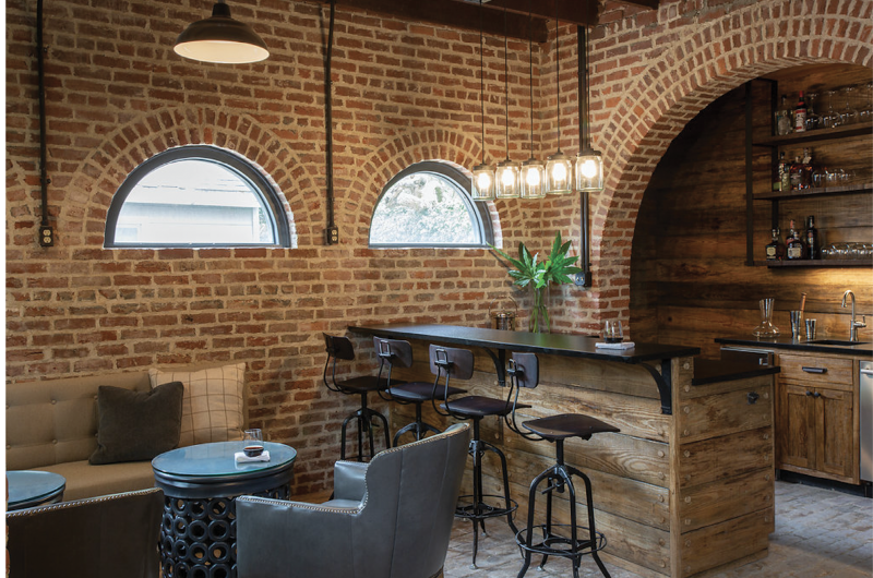 """Encircle the Squares - Since arches dominate the ground floor of this carriage house, designer Kristin Peake echoed the motif with cylindrical side tables and pendant lights and round mirrors to soften the hard lines of the floor plan and exposed brickwork.  Location: South of Broad  (dependency of the Porcher-Simonds House, circa 1856, owned by Kristy and Rick Schultz)  Issue: September 2019,  """"One Gorgeous Garage""""  Photographer:  Julia Lynn"""
