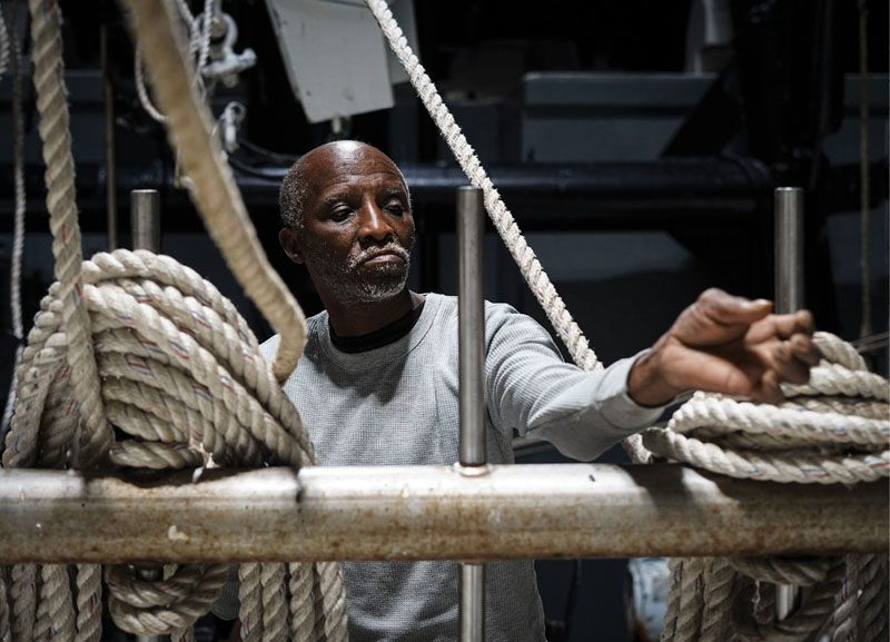 "and Carl Lee Jefferson ready the lines and winches for the first trawl. ""This is dangerous work,"" says Stephen, pointing to the outriggers above. ""I know guys who have been taken up with the ropes."""