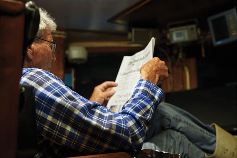 ...Captain Bubba Rector reads the paper as his trawler is on course for the day's first shrimping destination, typically within six miles from shore.
