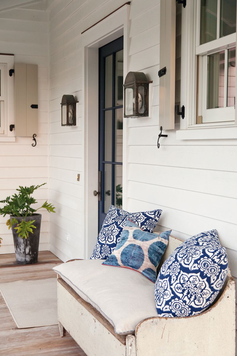 Pillows made from vintage textiles add a pop of color to the porch.