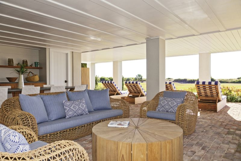 Down Under: The breezy plein-air living room under the house includes an outdoor fireplace and bar, with plenty of room for entertaining or just lounging in the shade.