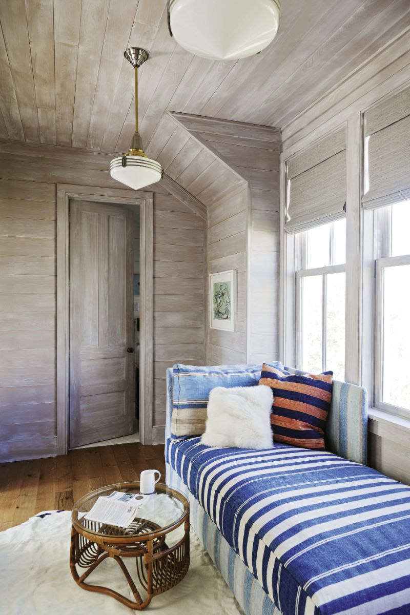 """Cozy bedrooms and bunks abound to fit in plenty of visitors, including a double-duty sleeper bench upholstered in a vintage dhurrie in the cedar-lined """"office"""""""