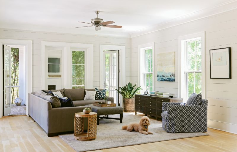 """Lap & Light: Shiplap walls throughout the main living and dining rooms give a """"buttoned-up"""" feel to the casual décor, says Lenox. Loads of natural light energize the airy rooms, and a calming palette of soft greys adds a sophisticated feel."""