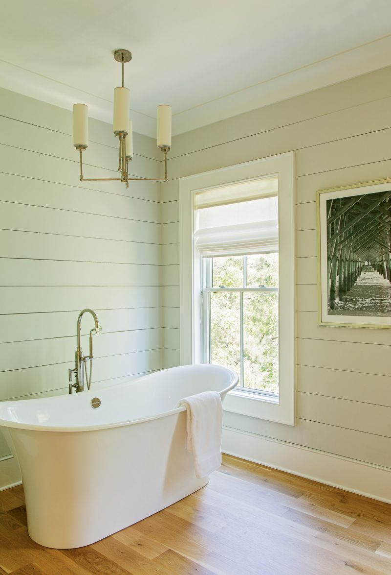 "Drawing a Bath: Frank and Lenox spent days redrawing the original plans for the master bath, which entailed moving the oversized walk-in shower to another wall, and perfecting the sight lines into the bath from the hallway and again into the adjoining dressing rooms. ""I love the sculptural aspect of the tub, contrasted with the angularity of the pendant light,"" says Lenox."