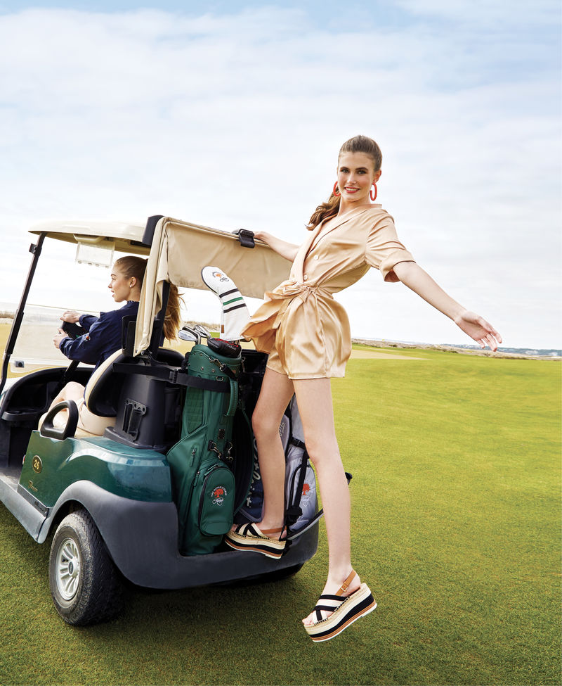 "Long Drive: (On Maddie, left) Julie Brown NYC ""Disco Tek"" top, $115 at Out of Hand; Tory Sport ruffle windbreaker, $158 at The Ocean Course at Kiawah Island Pro Shop; ""Luxe"" shorts in ""taupe,"" $72 at Maris DeHart; Little Fish Boateak coin pearl studs, $24 at Woodhouse Day Spa; (on Sara, right) Lost + Wander ""High Roller"" romper, $108 at Sapphire Boutique; Ink + Alloy coral beaded hoops, $27 at Out of Hand; Tory Burch platform espadrille sandal, $258 at Gwynn's of Mount Pleasant"