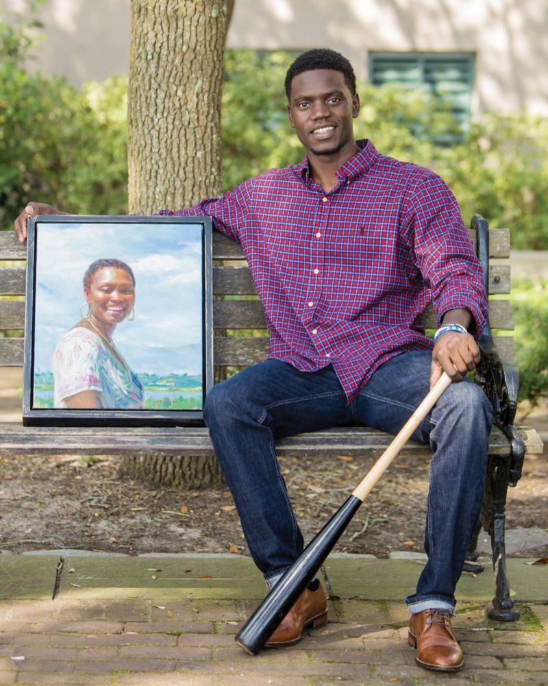 Chris Singleton, a former professional baseball player who is now an inspirational speaker and employee of the RiverDogs, with a portrait of his late mother painted by Ricky Mujica.
