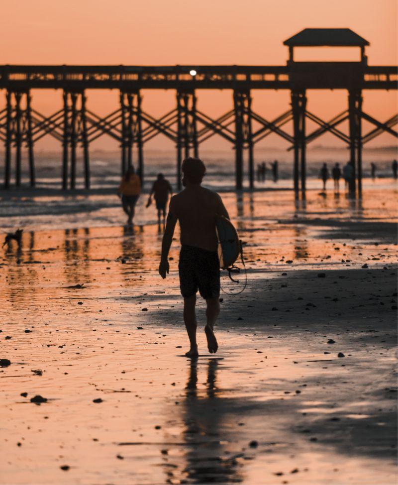Dusk backlights rocky new sand from beach renourishment.