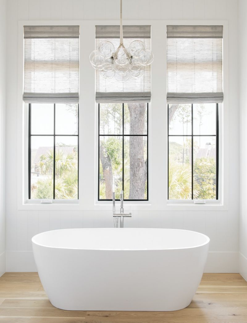 In the adjoining bathroom, a large bubble chandelier from Pelle hangs above a Mirabelle freestanding tub.