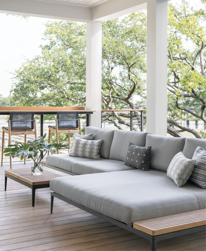 """Modern Mood: The Grid sectional and chairs from Gloster mix modern and organic, steel and teak, all accented by neutral greys and whites in the outdoor living room. """"The back of the house is literally a nature wonderland,"""" says Lenox. """"I felt the dichotomy of incorporating very modern furniture into such a natural landscape was interesting and unexpected."""""""