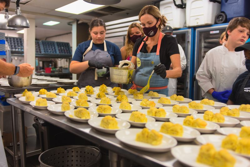 Little chefs Chloe Farkouh and Claudia Hassell assist Carrie Morey in plating vegan biscuits with curry.