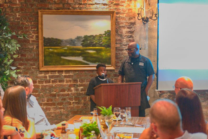Grant Higgins addresses the crowd with his big chef partner Rodney Scott