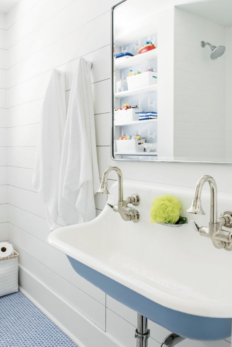Shiplap walls, penny-tile floors, simple towel hooks, and a trough sink make for a splash-safe (and stylish) backdrop to bath time.
