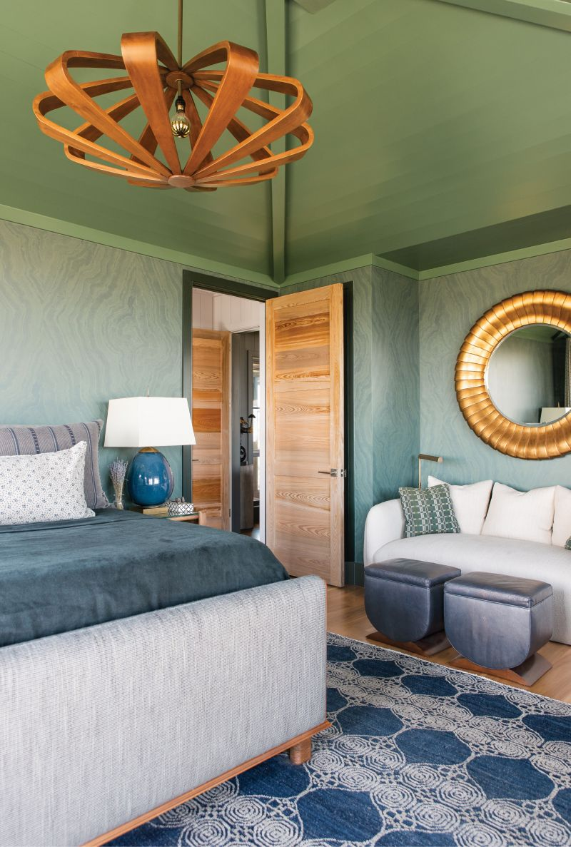 "Into the Deep: A wood ceiling painted in a custom green hue encapsulates this cozy master bedroom, replete in deep blues that mimic the ocean beyond. A sunken cypress door and the ""Remus"" saucer pendant light by Arteriors contrast with the wallpaper, designed by Apparatus in collaboration with ZAK+FOX, that provides a soothing backdrop for a peaceful night's rest."
