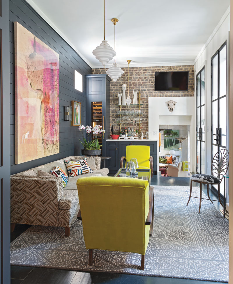 "Trading Spaces: Formerly a slim galley kitchen, this ""hyphen"" connecting the Ansonborough single house to its guest suite was transformed into a chic lounge space, complete with wet bar."