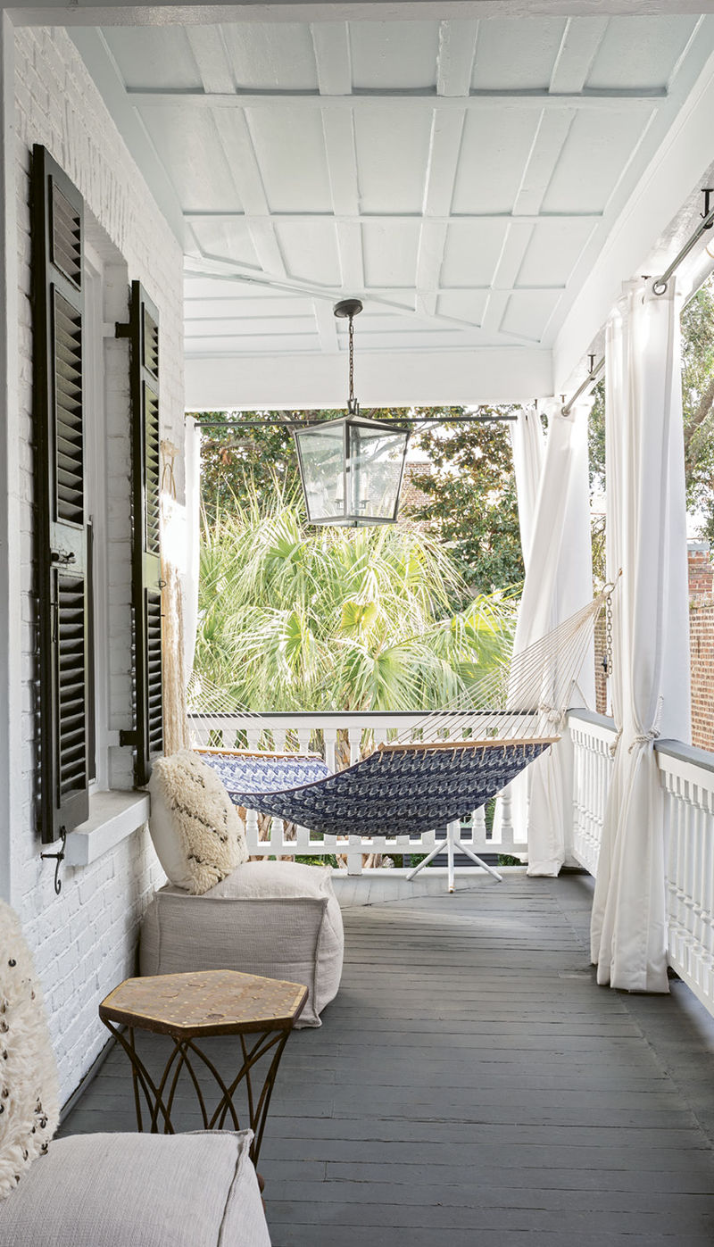 A Relaxing Perch: The upstairs porch provides a pleasant respite from everyday cares, with a hammock and Restoration Hardware Moroccan wedding pillows precisely positioned to take in the treetop views.