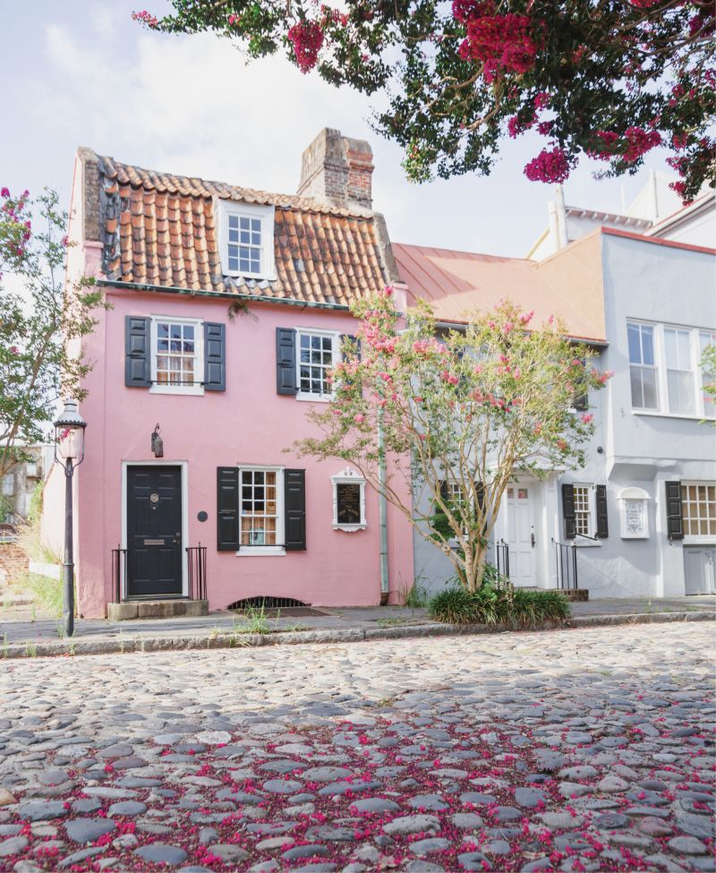 Tickled Pink: Crepe myrtles shower the cobblestones in front of the Pink House with blossoms.