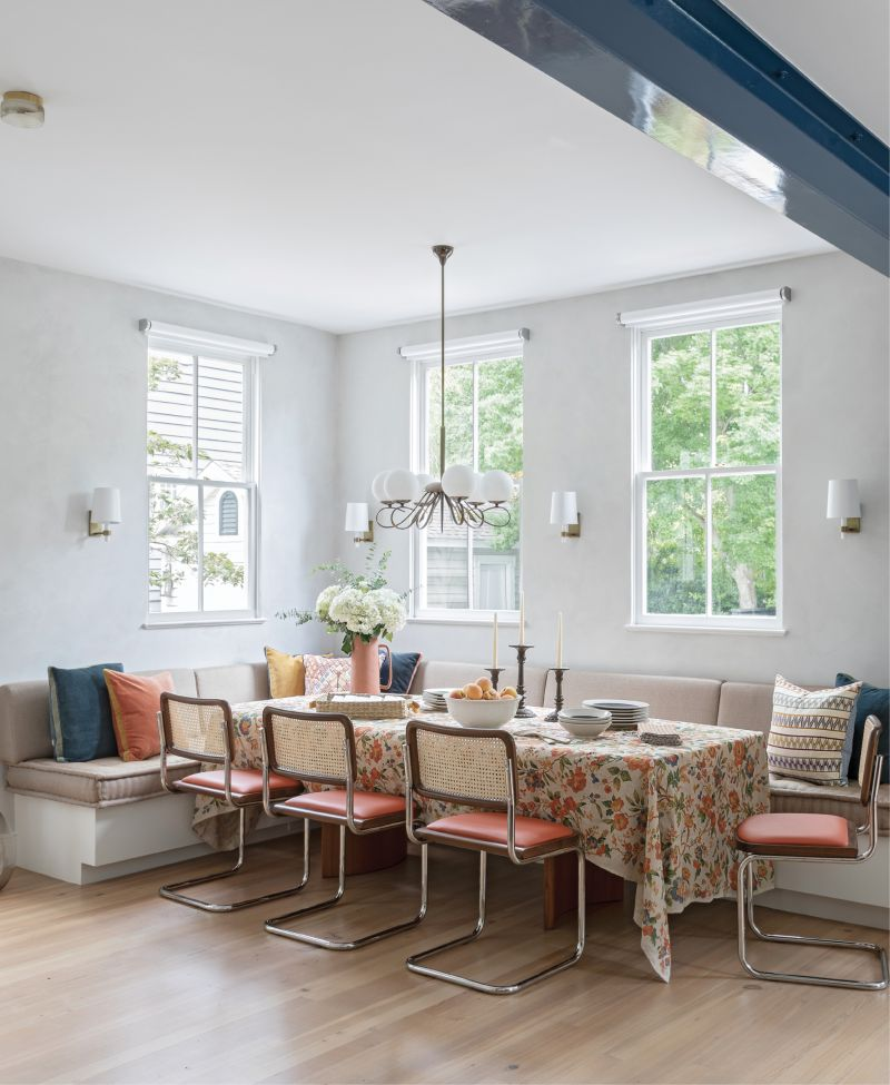 Beam It Up: Previously a screened-in porch, this dining space in the now-enlarged kitchen is the perfect place for the Newmans's two daughters and their friends to hang out, or to gather the family for a meal. A long banquette extends the full width of the room providing plenty of space to spread out. Marcel Breuer-designed Cesca chairs add mid-century flair, and industrial motorized shades from J Geiger complement the room's central feature—the architectural steel beam that traverses the space.