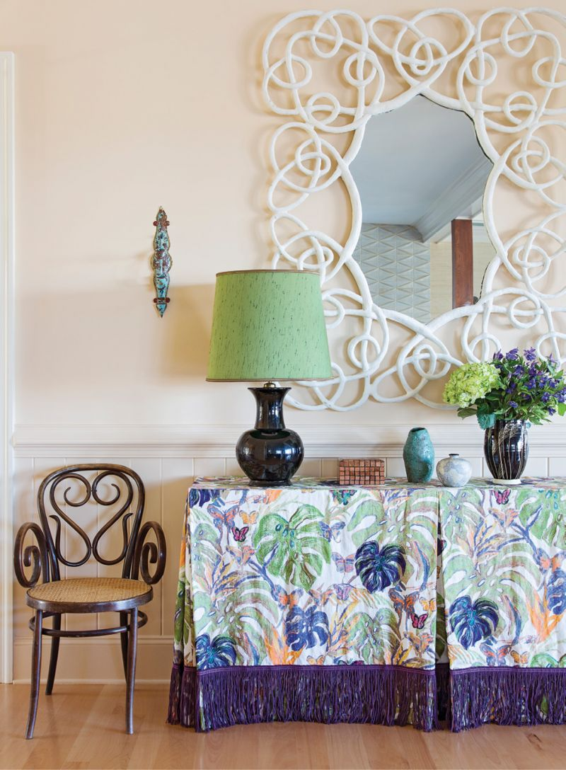 """Hranowsky knew this whimsical mirror, found at the New York Design Center, commanded a central spot. She balanced its playfulness with a bentwood Thonet chair beside the console, covered in the lush """"Monstera"""" fabric by Hunt Slonem for Kravet, adding further swirl and fun in the entry hall."""